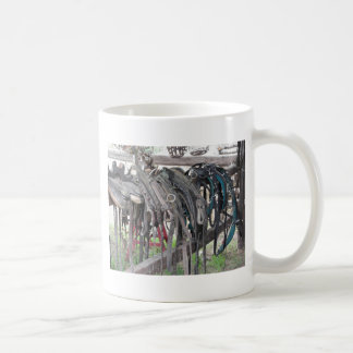 Worn leather horse bridles hanging on wooden fence coffee mug