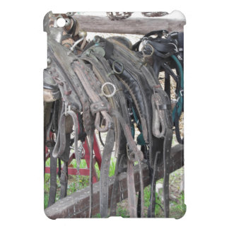 Worn leather horse bridles hanging on wooden fence iPad mini cover