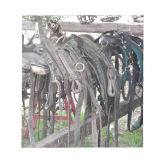 Worn leather horse bridles hanging on wooden fence notepad