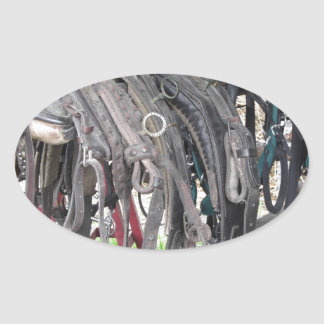 Worn leather horse bridles hanging on wooden fence oval sticker