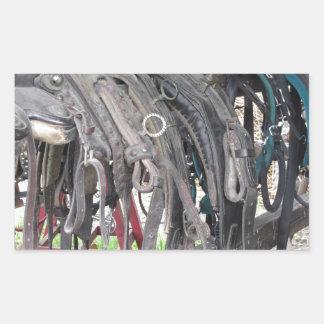 Worn leather horse bridles hanging on wooden fence rectangular sticker