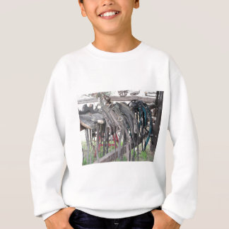 Worn leather horse bridles hanging on wooden fence sweatshirt