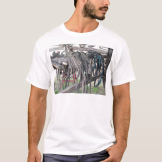 Worn leather horse bridles hanging on wooden fence T-Shirt