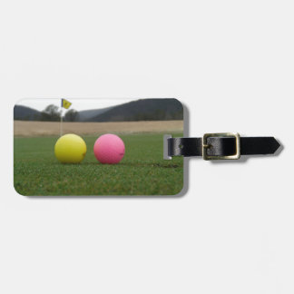 yellow and pink golf balls, bag tag