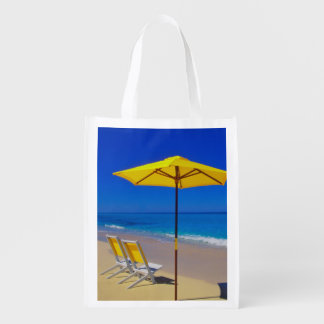 Yellow beach umbrella and chairs on pristine