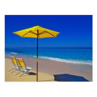 Yellow beach umbrella and chairs on pristine postcard