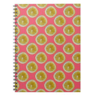 Yellow lemon slices on pink notebooks