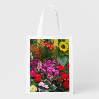 Yellow picket fence with flower garden in reusable grocery bags