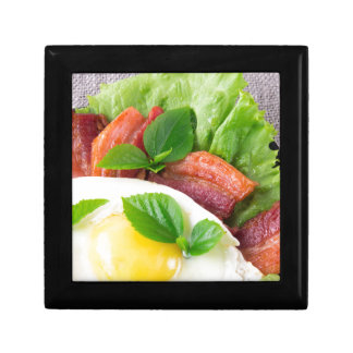 Yolk, fried bacon, herbs and lettuce close-up gift box