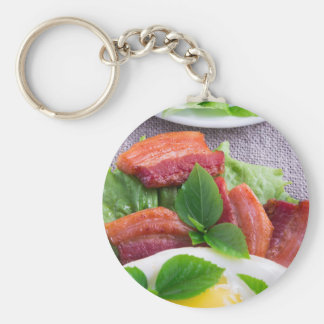 Yolk, fried bacon, herbs and lettuce close-up key ring