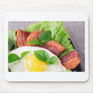 Yolk, fried bacon, herbs and lettuce close-up mouse pad
