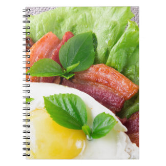 Yolk, fried bacon, herbs and lettuce close-up notebook