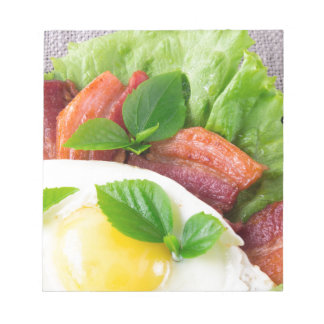 Yolk, fried bacon, herbs and lettuce close-up notepad