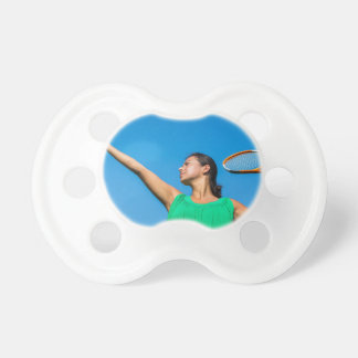Young dutch woman with tennis racket and ball baby pacifiers