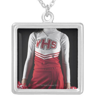 Young female cheerleader holding pom-poms, mid silver plated necklace