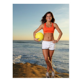young fit pretty female holding a volleyball at postcard