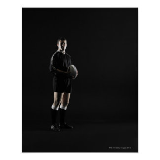 Young man holding rugby ball, portrait poster