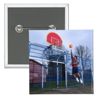 Young man playing basketball outdoors 15 cm square badge
