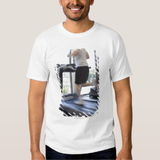 Young man running on a treadmill at health club, T-Shirt