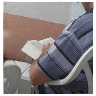 Young man sitting on chair reading book printed napkin