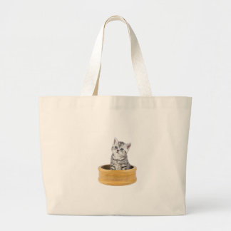 Young silver tabby cat sitting in wooden bowl large tote bag