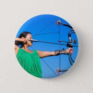Young woman aiming arrow of compound bow 6 cm round badge