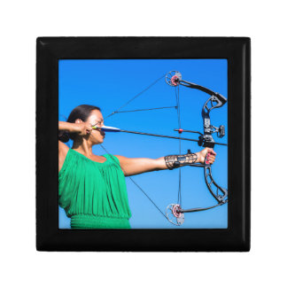 Young woman aiming arrow of compound bow gift box