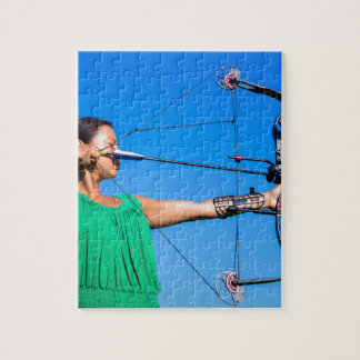 Young woman aiming arrow of compound bow jigsaw puzzle