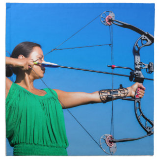 Young woman aiming arrow of compound bow napkin