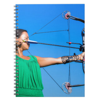 Young woman aiming arrow of compound bow notebooks