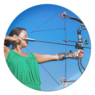 Young woman aiming arrow of compound bow plate