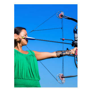 Young woman aiming arrow of compound bow postcard