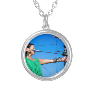 Young woman aiming arrow of compound bow silver plated necklace