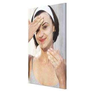 Young woman exfoliating face, smiling, portrait, stretched canvas prints