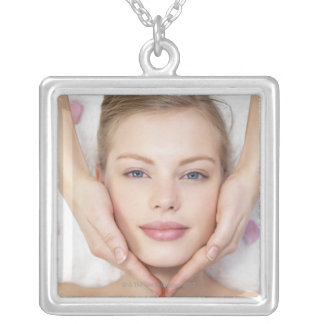 Young woman getting massage silver plated necklace