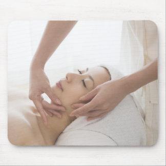 Young woman having facial massage mouse pad
