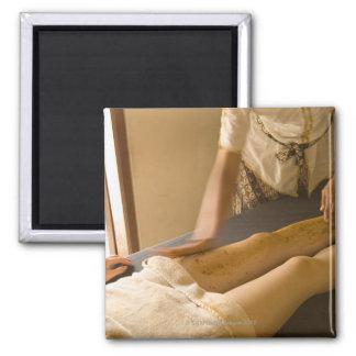 Young woman having leg massage square magnet