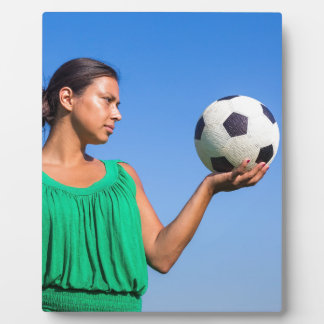 Young woman holding football on hand with blue sky plaques