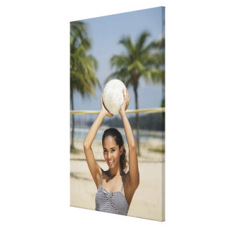 Young woman holding volleyball and smiling at canvas print