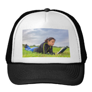 Young woman lying in grass reading book cap