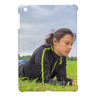 Young woman lying in grass reading book case for the iPad mini