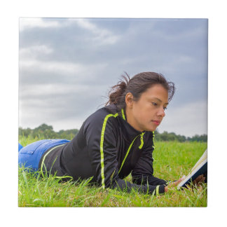 Young woman lying in grass reading book ceramic tile