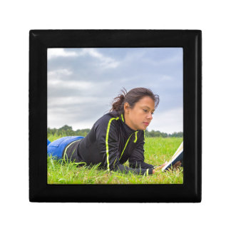 Young woman lying in grass reading book gift box