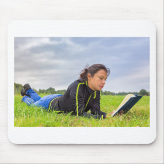 Young woman lying in grass reading book mouse pad