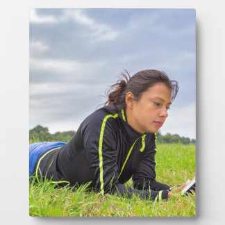 Young woman lying in grass reading book photo plaques