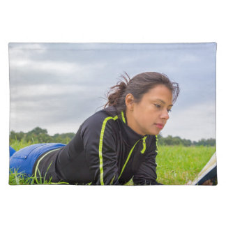 Young woman lying in grass reading book placemat