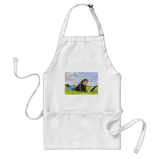 Young woman lying in grass reading book standard apron