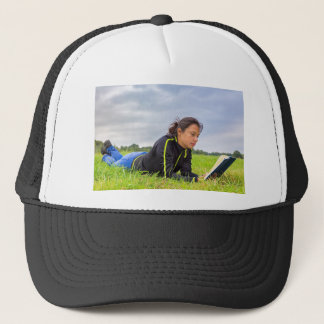 Young woman lying in grass reading book trucker hat