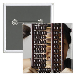 Young woman peering through abacus. 15 cm square badge