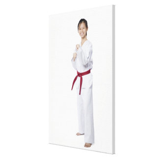 Young woman practicing karate and smiling stretched canvas prints